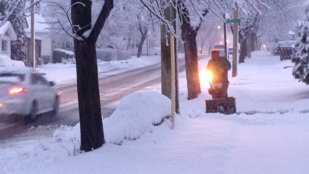 A man uses his snowblower to clear his driveway on Rockwood Avenue in Thunder Bay.