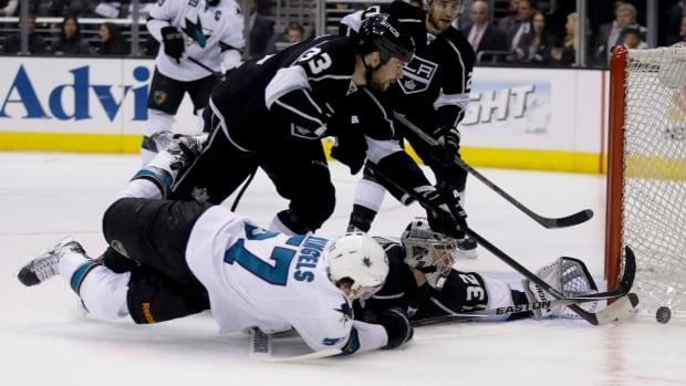 Los Angeles Kings goalie Jonathan Quick blocks a shot by San Jose Sharks centre Tommy Wingels as Willie Mitchell looks on during the first period in Game 4 of an NHL hockey first-round playoff series in Los Angeles on Thursday, April 24.