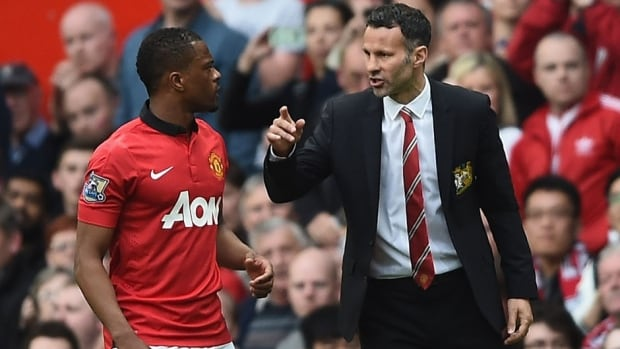 Manchester United manager Ryan Giggs, right, speaks with Patrice Evra during Saturday's Premier League match against Norwich City at Old Trafford. Giggs won his managerial debut 4-1, thanks in large part to Wayne Rooney's two-goal performance.
