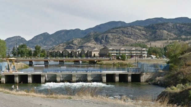 An image from Google Street View shows a view of a dam and a bridge across the Okanagan River near the community of Okanagan Falls, also known as OK Falls.