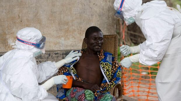 A patient with Ebola is comforted by Doctors Without Borders medical professionals.