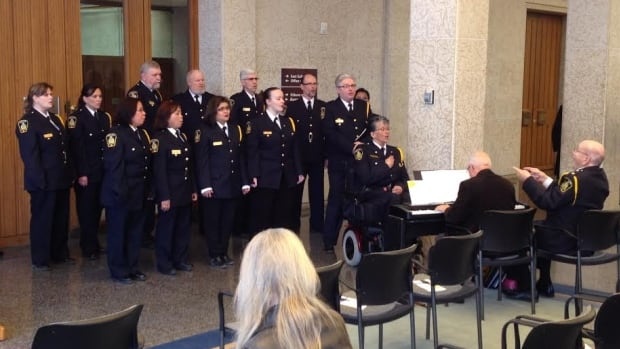 The Winnipeg Police Service choir sings inside city hall on Monday as part of the National Day of Mourning.