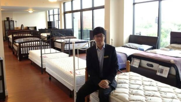 Chen Qing poses with his mattresses in his penthouse showroom.
