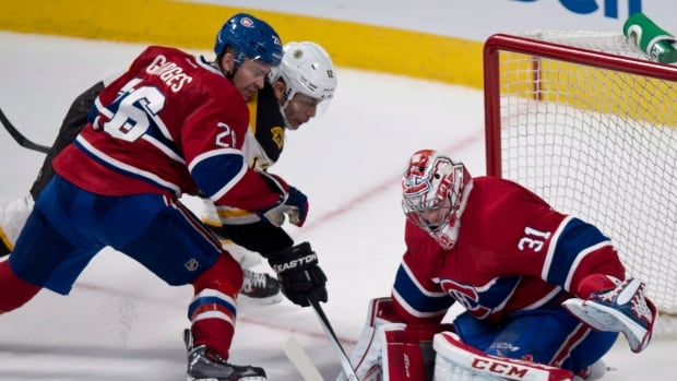 Montreal Canadiens goalie Carey Price stops a shot by Boston Bruins forward Jarome Iginla as Canadiens defenceman Josh Gorges covers during a Dec. 5, 2013 game at Bell Centre.