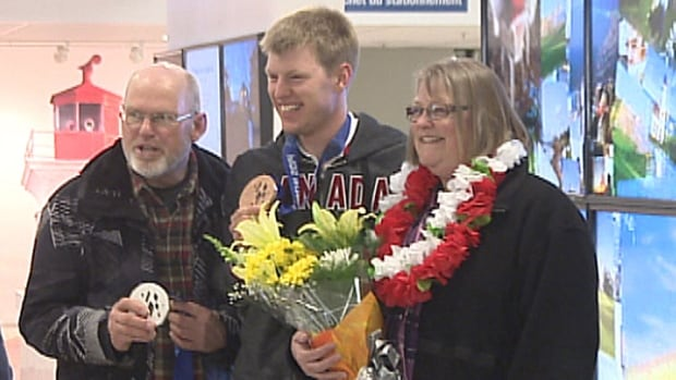 Paralympian Mark Arendz poses with his parents and his two medals on his return to P.E.I. after the Paralympic games in Sochi.