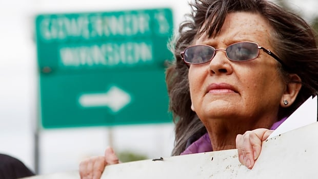 Fannie Bates of Oklahoma City holds a sign urging Gov. Mary Fallin to issue a stay in the execution of two inmates Tuesday. The state has changed protocols twice this year, now giving it five drug options to use in executing people.