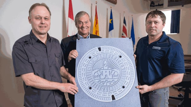 Robert Scullion, left, who designed the winning manhole cover, poses with Fredericton Mayor Brad Woodside and Trent Brewer, manager of the city's water and sewer division.