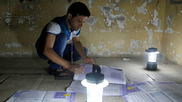 Employees of Iraq's independent electoral commission count ballots Wednesday following the first set of parliamentary elections since U.S. forces withdrew.