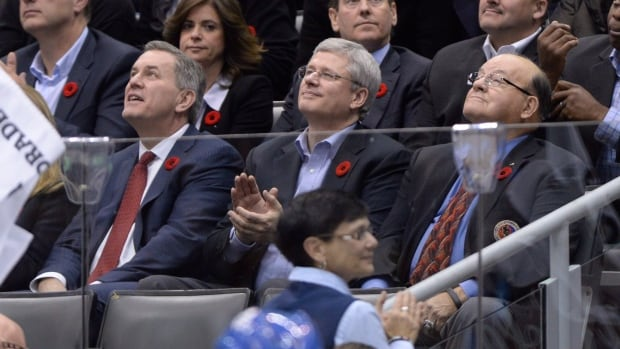 Prime Minister Stephen Harper, centre, watches a hockey game in Toronto with Maple Leaf Sports and Entertainment CEO and president Tim Leiweke, left, and legendary former NHL coach Scotty Bowman on Nov. 8, 2013.