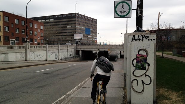 New signs at a dangerous St-Denis Street underpass encourage cyclists and pedestrians to share the sidewalk.
