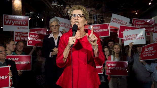 Ontario Liberal Leader Kathleen Wynne, right, speaks as her wife Jane Rounthwaite looks on during a rally in Toronto on Friday. Wynne called an election for June 12 after NDP Leader Andrea Horwath announced that her party would not support the Liberal's budget.