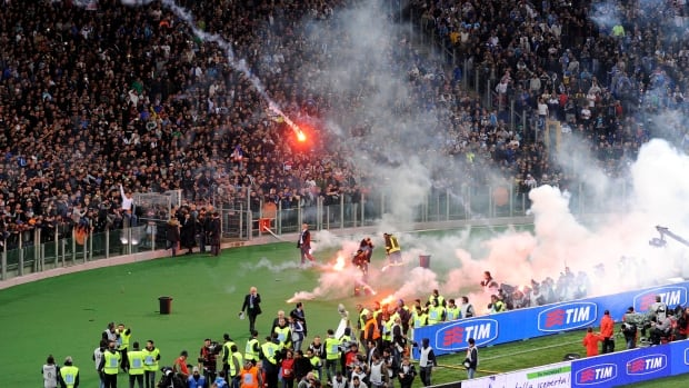 Napoli fans throw flares prior to the start of Italian Cup final match between Fiorentina and Napoli in Rome's Olympic stadium.