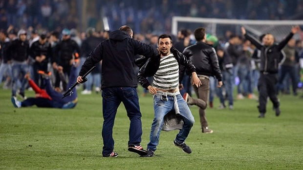 An Italian policeman, front, chases a Napoli fan out of the pitch at the end of the Italian Cup final match between Fiorentina and Napoli in Rome's Olympic stadium on Saturday.
