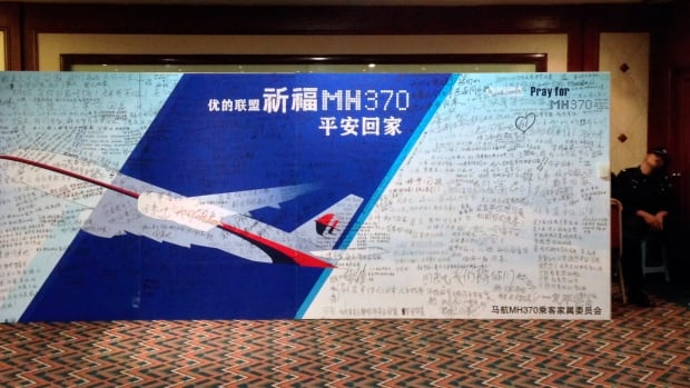 A policeman takes a nap beside a board written with messages for passengers onboard the missing Malaysia Airlines Flight MH370 at Lido Hotel in Beijing on Friday.