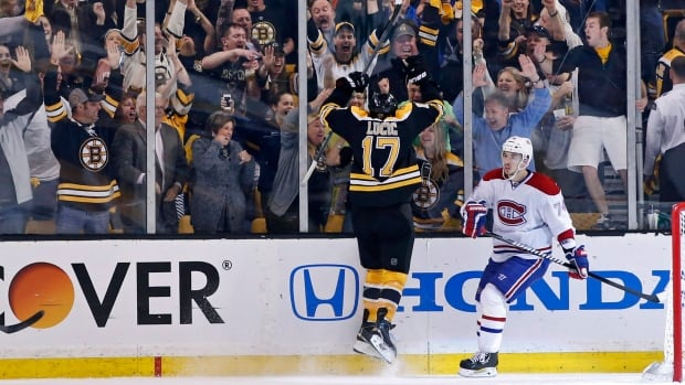 Boston Bruins left wing Milan Lucic (17) celebrates his goal with fans as Montreal Canadiens defenseman Alexei Emelin (74) skates away during the third period in Game 2 of their second-round playoff series in Boston on Saturday The Bruins won 5-3.
