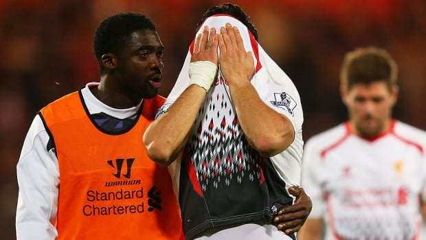 Kolo Toure, left, of Liverpool consoles dejected teammate Luis Suarez, middle, following their team's 3-3 draw with Crystal Palace during English Premier League actio  in London on Monday. Seeking the league title, Liverpool is one point ahead of Manchester City, which has a game in hand.
