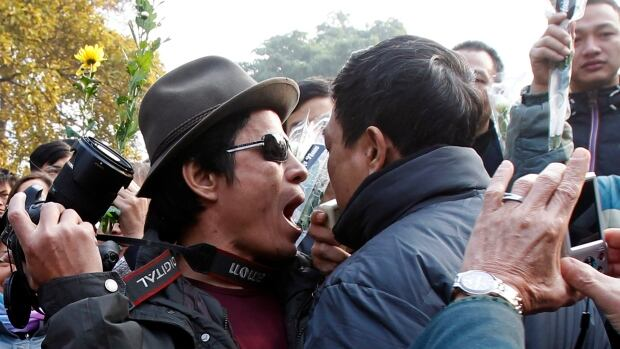 Political blogger Nguyen Huu Vinh, left, argues with a policeman during a gathering in Hanoi in January. Vietnamese authorities arrested Vinh and another blogger on Monday for posting critical articles about the government on the Internet.