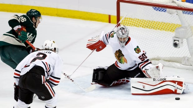 Chicago Blackhawks goalie Corey Crawford deflects a shot by Minnesota's Erik Haula, but the Finnish left wing would later put the Wild on the board.