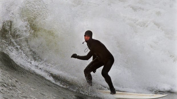 A surfer takes advantage of foul weather as he rides a wave off Cow Bay, N.S. near Halifax. The best surfing in Nova Scotia is from August to late November during hurricane season as well as when winds blow northeasterly.