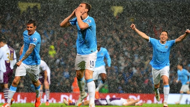 Edin Dzeko, middle, of Manchester City celebrates scoring the opening goal during the Premier League match against Aston Villa in Manchester on Wednesday. Dzeko scored twice in City's 4-0 win to move them atop the EPL standings.