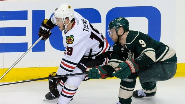 "Blackhawks centre Jonathan Toews, left, is bothered that his team has managed just 61 shots in the first three games against Mikko Koivu, right, and the Wild. ""We're still looking for the type of game we know we can play and we just haven't brought it yet."""