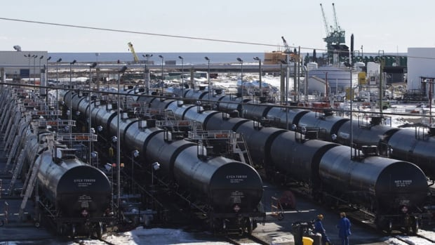 Oil workers inspect rail cars carrying crude oil at an oil yard. The U.S. government issued an emergency order on Wednesday requiring railroads to inform state officials ahead of time if high-volume shipments of crude are being shipped through.
