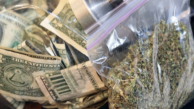 A bag of marijuana sits next to a money jar at BotanaCare in Northglenn, Colorado. Colorado legislators have approved a financial system designed to allow pot businesses to access banking services.