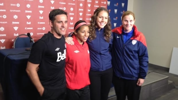 Members of Canada's national women's soccer team, including coach John Herdman, left, pose for photos and speak to reporters in Winnipeg on Wednesday.