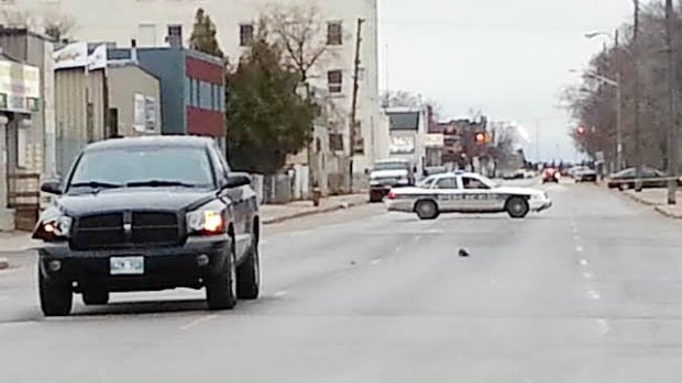 A black truck with a damaged front corner, and a shoe in the middle of the street, mark the scene on Thursday where a pedestrian was hit.