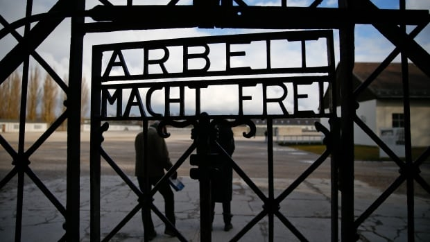 "Visitors walk past the main gate with the sign ""Arbeit macht frei"" (work sets you free) at Dachau near Munich, Germany. A school board in Rialto, Calif., was forced to backtrack on an eight-grade school assignment that asked students whether they believed the Holocaust was real."