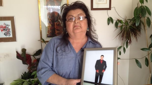 Cindy Kahm holding a picture of her son, Jeff Caron. Caron was killed in 2012 after a trench collapse in Burnaby, BC.
