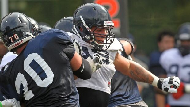 Brent Urban, of Mississauga, Ont., is seen breaking through a block during a practice session in Charlottesville, Virginia, last year. The 23-year-old was drafted by the NFL's Baltimore Ravens on Saturday.