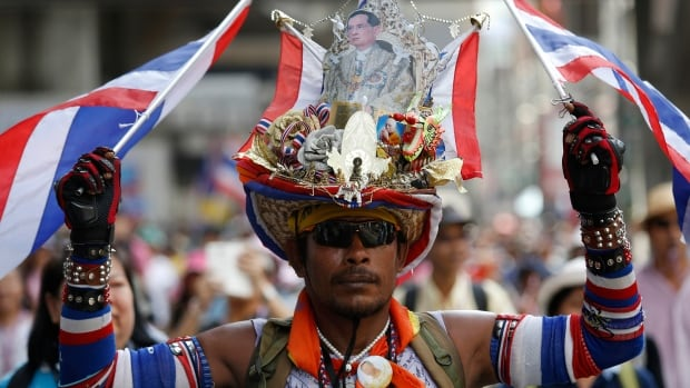 An anti-government protester wears a hat with a picture of Thailand's King Bhumibol Adulyadej as he joins thousands of others marching through central Bangkok on Friday. Thousands of royalist protesters fanned out across Thailand's capital to try to bring down a caretaker government after a court threw Prime Minister Yingluck Shinawatra out of office and an anti-graft agency indicted her for negligence.