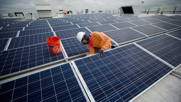 Neil Black works on the installation of a solar panel array atop an IKEA store in Miami. IKEA is a big adopter of solar and Wal-Mart has pledged to double its solar installations.