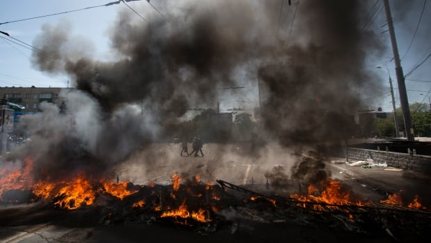 A pile of tires aimed at preventing Ukrainian military vehicles from passing through, burns in the centre of Mariupol in eastern Ukraine on Saturday.