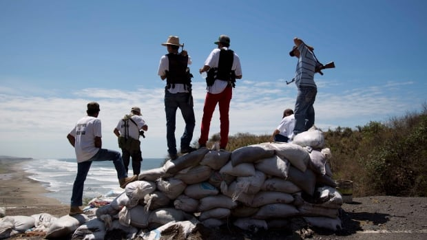 Armed men belonging to the Self-Defense Council of Michoacan (CAM) look out toward the sea as they guard a checkpoint set up by the self-defense group in Chuquiapan on the outskirts of the seaport of Lazaro Cardenas in western Mexico on Friday, May 9.