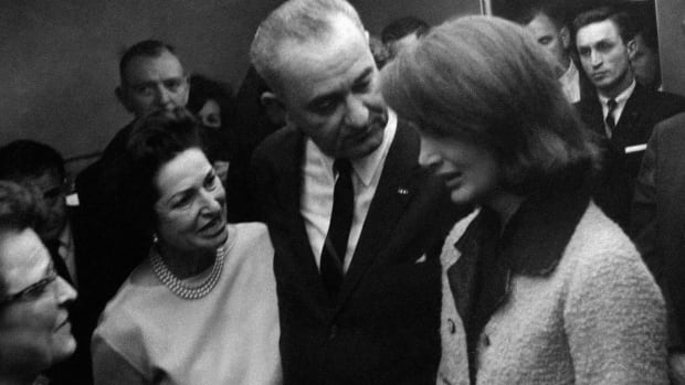 "In this Nov. 22, 1963, file photo, Thomas ""Lem"" Johns, background right, stands behind President Lyndon B. Johnson and his wife, Lady Bird, wearing a necklace, as they console Jacqueline Kennedy, right, moments after Johnson was administered the oath of office in Dallas. Johns, a former secret service agent present during the assassination of John F. Kennedy and swearing in of Johnson, has died. He was 88."