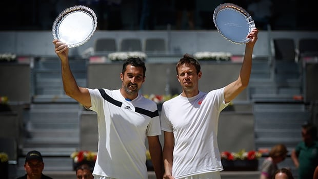 Nenad Zimonjic from Serbia, left, and Daniel Nestor from Canada hold up their trophies after winning the doubles final match against Bob and Mike Bryan from the U.S. at Madrid Open tennis tournament on Sunday.