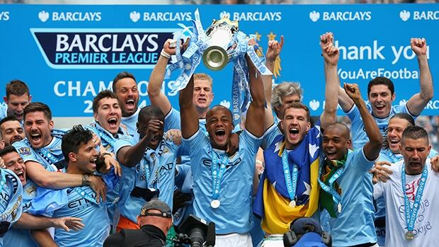 Vincent Kompany of Manchester City lifts the Premier League trophy at the end of the Barclays Premier League match between Manchester City and West Ham United at the Etihad Stadium on Sunday in Manchester, England.