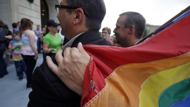 Shon DeArmon, right, puts his arm around his partner James Porter while holding a flag outside the Pulaski County Courthouse in Little Rock, Ark., on May 12. The state's largest county began issuing gay marriage licenses following a judge's ruling overturning Arkansas' constitutional ban on same-sex marriage.