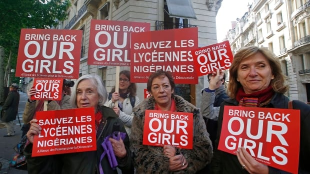 Women hold signs during a rally near the Nigerian embassy in Paris to raise to show support for the release of the kidnapped girls in Nigeria on Monday, May 12, 2014. Canada is joining an international effort to free almost 300 schoolgirls kidnapped by a west African Islamic extremist group.