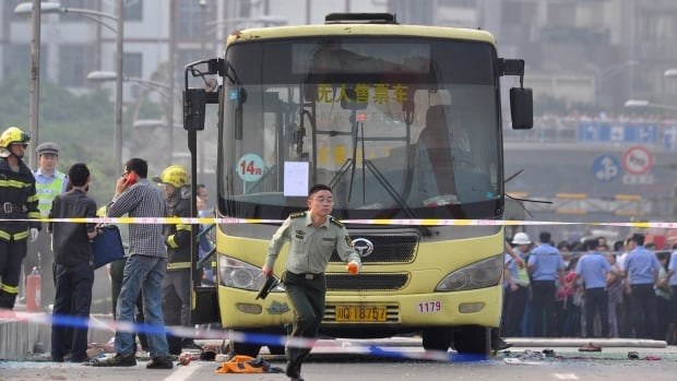 A paramilitary policeman runs in front of a bus after it was set on fire on a bridge in Yibin, Sichuan province, on Monday. According to Xinhua News Agency, one person was killed and 77 were sent to hospital in the accident.