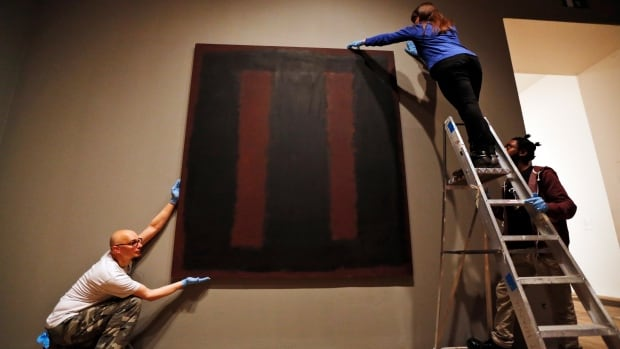 Tate Modern employees in London adjust Mark Rothko's Black on Maroon, which went back on display Tuesday, more than a year and a half after it was defaced with black ink by a vandal.