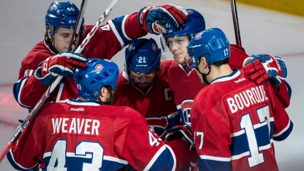 Montreal Canadiens' Nathan Beaulieu (40) celebrates after Montreal's first period goal by Lars Eller (81). Beaulieu, a former Hamilton Bulldog, got his first assist on the second Habs goal in his first NHL playoff game on Monday, May 12, 2014 in Montreal. THE CANADIAN PRESS/Paul Chiasson