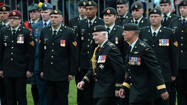 Gov. Gen. David Johnston and Maj.-Gen. Dean Milner take part in an inspection of Afghanistan war veterans during the National Day of Honour in Ottawa on May 9. In the 2013-14 fiscal year, Veterans Affairs spent $103,694 promoting tweets on one of its social media accounts.