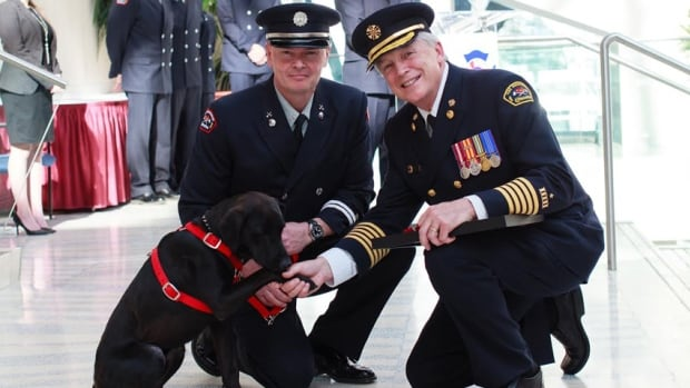 Rescue dog Grover joined the Edmonton Fire Rescue Services K9 Unit Tuesday. Here, he shakes a paw with fire chief Ken Block. Grover's handler, Capt. Murray Steedsman is on the dog's left.
