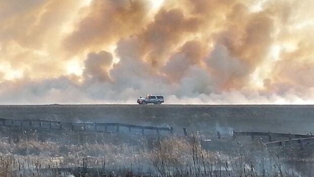 Smoke blazes from a grass fire near Riverside Cemetery.