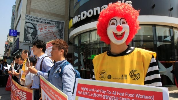 A protester dressed as Ronald McDonald participates in a rally to demand higher wages in Seoul on Thursday. Protests were planned in more than 30 countries, but the biggest turnout was in the U.S. where federal minimum wage is $7.25.