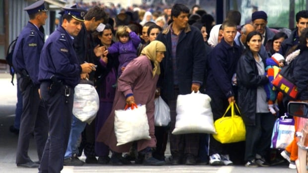 Macedonian police supervise as hundreds of ethnic Albanian refugees gather in Macedonia to be relocated to refugee camps after crossing from Kosovo May 18, 1999.