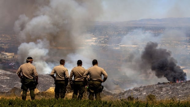 San Diego Sheriff's deputies watch as fire crews battle the Cocos Fire in San Marcos, California May 15, 2014. Wildfires were raging in southern California on Thursday, keeping thousands of residents and students away from their homes after San Diego county officials maintained evacuation advisories.